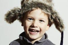 Lächelndes Kind in Pelz Hut Scherzt zufällige Winterart kleiner lustiger Junge der Mode Kindergefühl Stockbild