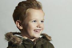 Lächelndes Kind Pelzhaube und Winterjacke Kinder in der erwachsenen Kleidung Kinder glückliche Winterart des kleinen Jungen Lizenzfreie Stockfotos