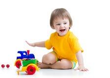 Lächelndes Kinderjungenkleinkind, das mit Spielwaren spielt Stockfoto