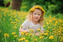 Lächelndes Kindermädchen im Löwenzahn winden auf Frühlingsblumenfeld Stockfoto