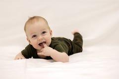 Lächelndes kleines Baby auf dem Bett Lizenzfreies Stockfoto