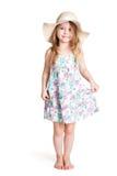 Lächelndes kleines blondes Mädchen, das großen weißen Hut und Kleid trägt Stockbild