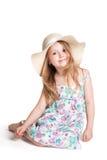Lächelndes kleines blondes Mädchen, das großen weißen Hut und Kleid trägt Stockfotografie
