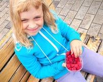Lächelndes kleines blondes Mädchen mit Himbeeren Stockfotos