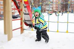 Lächelndes kleines Kind auf Spielplatz im Winter Stockbilder