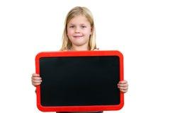 Lächelndes kleines Kind, das leeres schwarzes Brett hält lizenzfreie stockfotografie