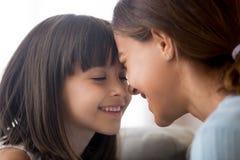Lächelndes kleines Kindermädchen, das zart Stirnen mit glücklichem berührt stockfotos
