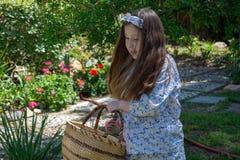 Lächelndes kleines Latina-Mädchen im Kleid des Gartens im Frühjahr mit Korb lizenzfreies stockfoto