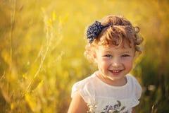 Lächelndes kleines Mädchen auf dem Feld Stockfotos