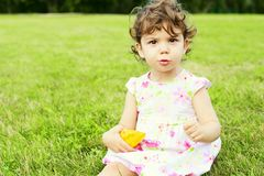 Lächelndes kleines Mädchen auf der Wiese stockfotografie