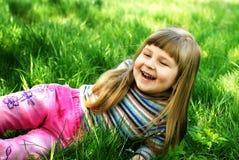 Lächelndes kleines Mädchen auf Gras Lizenzfreie Stockbilder