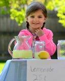 Lächelndes kleines Mädchen auf Limonadestand am Sommer Stockfotografie