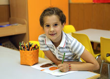 Lächelndes kleines Mädchen beim Zeichnen mit den Bleistiftfarben Lizenzfreie Stockbilder