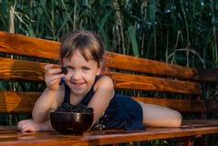 Lächelndes kleines Mädchen, das auf der Bank mit einer Brombeere in ihrer Hand liegt lizenzfreies stockfoto