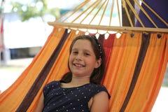 Lächelndes kleines Mädchen, das auf Hängematte während der Feiertage stillsteht Lizenzfreie Stockfotografie