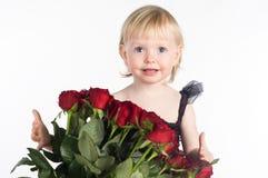 Lächelndes kleines Mädchen, das großen Blumenstrauß von roten Blumen empfängt Lizenzfreies Stockbild