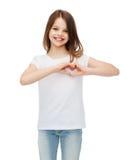 Lächelndes kleines Mädchen, das Herz mit den Händen zeigt stockfoto