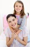 Lächelndes kleines Mädchen, das ihre Mutter umarmt Lizenzfreies Stockfoto