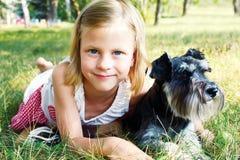 Lächelndes kleines Mädchen, das ihren Hund umarmt Stockfotografie