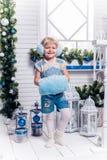 Lächelndes kleines Mädchen, das neben einem Weihnachtsbaum und einem Christm steht Stockfoto