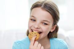 Lächelndes kleines Mädchen, das Plätzchen oder Keks isst Lizenzfreies Stockbild