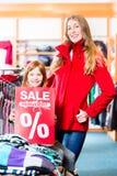 Lächelndes kleines Mädchen, das Verkaufsangebot fördert lizenzfreies stockfoto