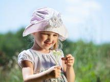 Lächelndes kleines Mädchen, das wilde Blumen hält Stockfoto