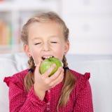 Lächelndes kleines Mädchen, das zu Hause Apple isst lizenzfreie stockfotografie