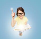Lächelndes kleines Mädchen in den Brillen mit Buch Stockfotografie