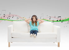 Lächelndes kleines Mädchen in den Kopfhörern, die auf Sofa sitzen Lizenzfreies Stockfoto