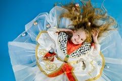 Lächelndes kleines Mädchen in der königlichen Kleidung Stockfoto
