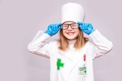 Lächelndes kleines Mädchen in der medizinischen Uniform und in den Gläsern, welche die Kamera lokalisiert betrachten stockbilder