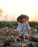 Lächelndes kleines Mädchen in einem Hut nahe einem trockenen Blumenbusch Stockfotos