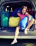 Lächelndes kleines Mädchen füllt die Koffer auf dem Auto vor dem lo Stockbilder