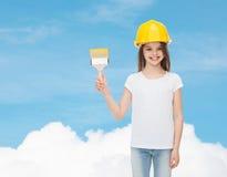 Lächelndes kleines Mädchen im Sturzhelm mit Pinsel Stockfotos