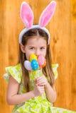 Lächelndes kleines Mädchen mit dem langen blonden Haar, das rosa und weißes Kaninchen oder die Häschenohren und -c$halten des Bün stockbild