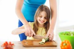 Lächelndes kleines Mädchen mit der Mutter, die Gurke hackt Stockfoto