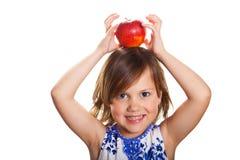 Lächelndes kleines Mädchen mit einem Apfel auf ihrem Kopf lizenzfreie stockfotos
