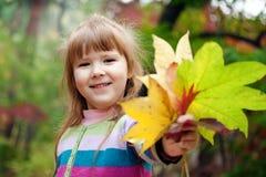Lächelndes kleines Mädchen mit gefallenen Blättern Lizenzfreie Stockbilder