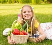 Lächelndes kleines Mädchen mit Gemüse und Beere lizenzfreies stockbild