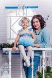Lächelndes kleines Mädchen mit ihrer älteren Schwester, die nahe bei einem Chr steht Lizenzfreies Stockfoto