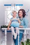 Lächelndes kleines Mädchen mit ihrer älteren Schwester, die nahe bei einem Chr steht Lizenzfreie Stockbilder