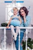 Lächelndes kleines Mädchen mit ihrer älteren Schwester, die nahe bei einem Chr steht Stockfotografie