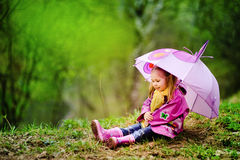 Lächelndes kleines Mädchen mit Regenschirm im Park Stockbild