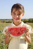 Lächelndes kleines Mädchen mit Scheibe der Wassermelone Stockbild