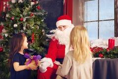 Lächelndes kleines Mädchen mit Weihnachtsmann und Geschenken Stockfotos