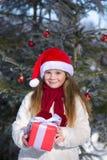 Lächelndes kleines Mädchen mit Winterwald des Weihnachtsgeschenks im Stockfoto