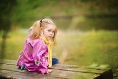 Lächelndes kleines Mädchen am regnerischen Tag im Park Lizenzfreies Stockbild