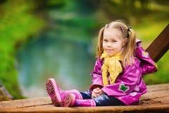 Lächelndes kleines Mädchen am regnerischen Tag im Park Lizenzfreie Stockfotos