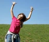LÄCHELNDES kleines Mädchen springt mit dem Rasen im Hintergrund Stockbild